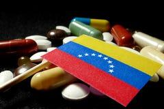 Της Βενεζουέλας σημαία με το μέρος των ιατρικών χαπιών που απομονώνεται στη μαύρη πλάτη Στοκ Εικόνες