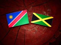 Της Ναμίμπια σημαία με την τζαμαϊκανή σημαία σε ένα κολόβωμα δέντρων Στοκ φωτογραφίες με δικαίωμα ελεύθερης χρήσης
