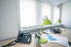 Τηλέφωνο και πράσινοι λαμπτήρες σε ένα γραφείο στοκ εικόνα
