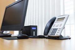 Τηλέφωνο και υπολογιστής στην επιτραπέζια εργασία της υπηρεσίας δωματίων Στοκ Φωτογραφία