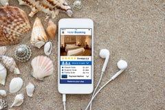 Τηλέφωνο με app τα κοχύλια οθόνης κράτησης ξενοδοχείων και άμμου ακουστικών Στοκ Εικόνες
