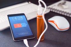 Τηλέφωνο που χρεώνει με την ενεργειακή τράπεζα πέρα από το γραφείο στοκ φωτογραφία με δικαίωμα ελεύθερης χρήσης