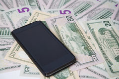 Τηλέφωνο σε ένα υπόβαθρο των χρημάτων στοκ εικόνες