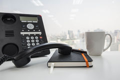 Τηλέφωνο IP και ένα μαύρου σημειωματάριο φλιτζανιών του καφέ και Στοκ φωτογραφία με δικαίωμα ελεύθερης χρήσης