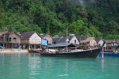 Τη βάρκα Longtail που σταθμεύουν στη θάλασσα έχει το παλαιά χωριό και το δάσος στο υποστήριγμα Στοκ Εικόνες