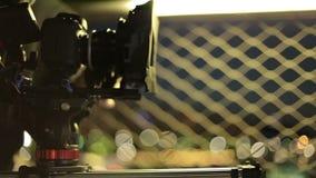 Τηλεοπτική κάμερα dslr που προωθεί στον ολισθαίνοντα ρυθμιστή με τα όμορφα φω'τα στο υπόβαθρο πίσω από την τηλεοπτική παραγωγή σκ απόθεμα βίντεο
