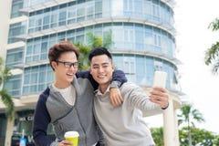 Τηλεοπτική κλήση νεαρών άνδρων δύο που χρησιμοποιεί το smartphone Στοκ Φωτογραφία
