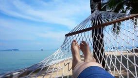 Τηλεοπτικό POV των ποδιών που ταλαντεύονται σε μια αιώρα στο δέντρο καρύδων Χαλάρωση στην παραλία της Ταϊλάνδης απόθεμα βίντεο