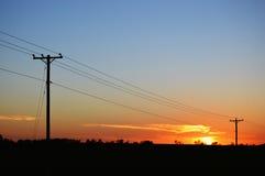 Τηλεφωνικοί πόλοι στο ηλιοβασίλεμα Στοκ Φωτογραφίες