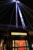 Τηλεφωνικός θάλαμος του Λονδίνου κάτω από τη γέφυρα Στοκ Εικόνες