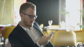 Τηλεφωνικός περιμένοντας επιχειρηματίας εκμετάλλευσης ατόμων στη συνεδρίαση στο εστιατόριο φιλμ μικρού μήκους