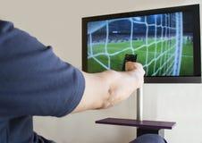 Τηλεχειρισμός TV εκμετάλλευσης χεριών Στοκ Φωτογραφίες