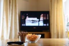 Τηλεόραση, TV που προσέχει (κινηματογράφος) με τα πρόχειρα φαγητά που βρίσκονται στον πίνακα Στοκ Εικόνες