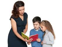 Τη μητέρα και τα παιδιά της που διαβάζονται το βιβλίο Στοκ Φωτογραφία