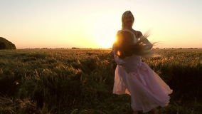Τη νέα γυναίκα με το κορίτσι γυρίζουν στον τομέα στο ηλιοβασίλεμα φιλμ μικρού μήκους
