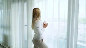 Τη νέα ξανθή παραμονή γυναικών που χαλάρωσαν κοντά σε μεγάλο το παράθυρο με ένα φλυτζάνι απόθεμα βίντεο