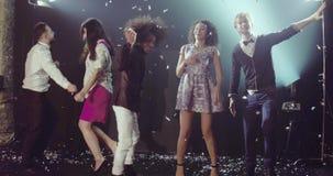 Τη νύχτα ομάδα λεσχών χορεύοντας φίλων που παρουσιάζουν συγκινήσεις της ευτυχίας φιλμ μικρού μήκους