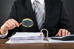 Τιμολόγιο επιθεώρησης επιχειρηματιών με την ενίσχυση - γυαλί στοκ φωτογραφίες