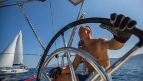 Τιμόνι πλοιάρχων νεαρών άνδρων κατά τη διάρκεια της φυλής γιοτ θάλασσας Στοκ Φωτογραφία