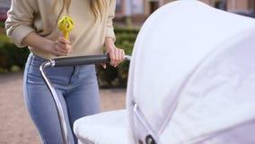 Τινάζοντας μέτωπο παιχνιδιών κουδουνισμάτων γυναικών νεογέννητου στον περιπατητή, αλληλεπίδραση babyhood απόθεμα βίντεο