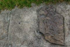 Τις πέτρες τοποθετούνται στο πάτωμα και τη χλόη τσιμέντου Στοκ εικόνες με δικαίωμα ελεύθερης χρήσης