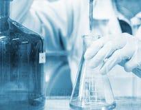Τιτλοδότηση χεριών επιστημόνων με την προχοΐδα και erlenmeyer τη φιάλη, την έννοια εργαστηριακής έρευνας επιστήμης και ανάπτυξης στοκ εικόνες
