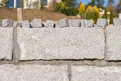 Τοίχος γρανίτη και πολλές μικρές πέτρες γρανίτη για το οδικό επίστρωμα Στοκ εικόνα με δικαίωμα ελεύθερης χρήσης