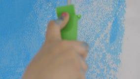 Τοίχος ζωγραφικής χεριών νέου κοριτσιού με τον κύλινδρο απόθεμα βίντεο