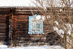 τοίχος κούτσουρων με το χαρασμένο παράθυρο του παλαιού αγροτικού σπιτιού Στοκ Εικόνες