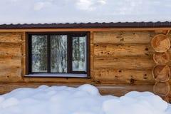 Τοίχος με ένα παράθυρο ενός ξύλινου σπιτιού στο χιόνι Στοκ Φωτογραφίες