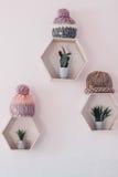 Τοίχος με τα hexagon ράφια και τα πλεκτά καπέλα Στοκ Φωτογραφία
