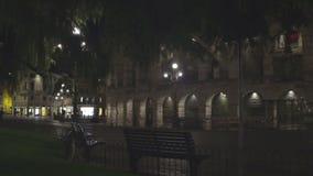 Τοίχος με τις αψίδες που φωτίζονται τη νύχτα, φω'τα των καφέδων πέρα από την εγκαταλειμμένη οδό απόθεμα βίντεο