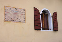 Τοίχος με το παλαιό ηλιακό ρολόι και το μεσαιωνικό παράθυρο Στοκ Φωτογραφία