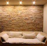 Τοίχος πετρών πλακών με τον καναπέ Στοκ Φωτογραφίες
