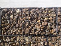 Τοίχος που προστατεύεται με τις πέτρες χαλικιών ποταμών στο πλέγμα σιδήρου στοκ εικόνες