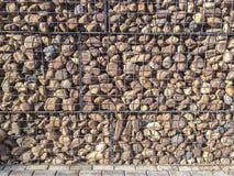 Τοίχος που προστατεύεται με τις πέτρες χαλικιών ποταμών στο πλέγμα σιδήρου στοκ εικόνα