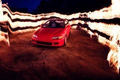 Τοίχος πυρκαγιάς πίσω από το κόκκινο αθλητικό αυτοκίνητο Στοκ Φωτογραφία