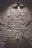 Τοίχος τούβλου grunge και ανώτατος λαμπτήρας επάνω από τον πίνακα Στοκ Εικόνες