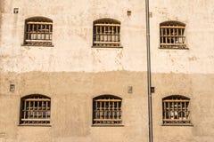 Τοίχος φυλακών με τα παράθυρα με τους φραγμούς Στοκ εικόνα με δικαίωμα ελεύθερης χρήσης