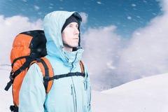 Τολμηρός νεαρός άνδρας με το σακίδιο πλάτης που στέκεται στη τοπ άποψη βουνών και που κοιτάζει έξω Ορειβασία, ακραίος αθλητισμός στοκ εικόνα