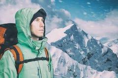 Τολμηρός νεαρός άνδρας με το σακίδιο πλάτης που στέκεται στη τοπ άποψη βουνών και που κοιτάζει έξω Ορειβασία, ακραίος αθλητισμός στοκ φωτογραφία με δικαίωμα ελεύθερης χρήσης