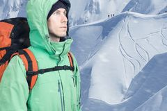 Τολμηρός νεαρός άνδρας με το σακίδιο πλάτης που στέκεται mountainside στην άποψη και που κοιτάζει έξω Ορειβασία, ακραίος αθλητισμ στοκ εικόνες