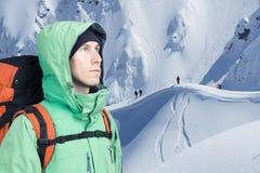 Τολμηρός νεαρός άνδρας με το σακίδιο πλάτης που στέκεται mountainside στην άποψη και που κοιτάζει έξω Ορειβασία, ακραίος αθλητισμ στοκ φωτογραφία