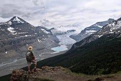 Τολμηρός οδοιπόρος ατόμων στον απότομο απότομο βράχο πέρα από τον παγετώνα της Κολούμπια Icefield και μια λίμνη moraine στοκ φωτογραφία