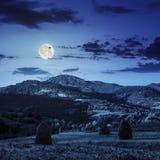 Τομέας με τη θυμωνιά χόρτου στη βουνοπλαγιά τη νύχτα Στοκ Φωτογραφίες
