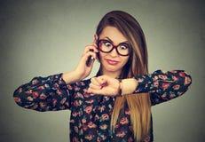 Τονισμένη έκπληκτη επιχειρησιακή γυναίκα που εξετάζει το wristwatch, που τρέχει αργά για τη συνεδρίαση Στοκ Φωτογραφία