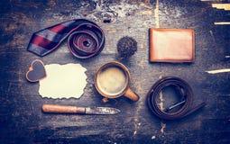 Τονισμένη έννοια της ημέρας του πατέρα του, ένα φλιτζάνι του καφέ, δεσμός, ζώνη, μαχαίρι, πορτοφόλι δέρματος, κείμενο θέσεων σε μ στοκ φωτογραφίες
