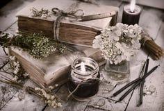 Τονισμένη ακόμα ζωή με τα μαύρα κεριά, τα παλαιά βιβλία και τα λουλούδια στις σανίδες Στοκ φωτογραφία με δικαίωμα ελεύθερης χρήσης