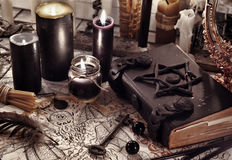 Τονισμένη ακόμα ζωή με το μαύρο μαγικό βιβλίο, το έγγραφο δαιμόνων και τα μαύρα κεριά Στοκ Φωτογραφία