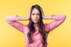 Τονισμένη απογοήτευση γυναίκα με τον πονοκέφαλο που απομονώνεται στο κίτρινο υπόβαθρο στοκ φωτογραφία